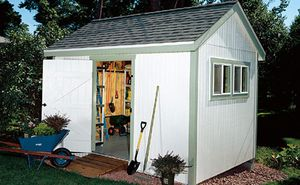 A white shed with green trim