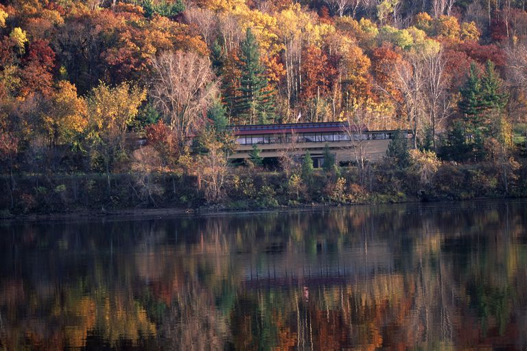 a long, low, wooden structure nestled in the woods on the banks of a river