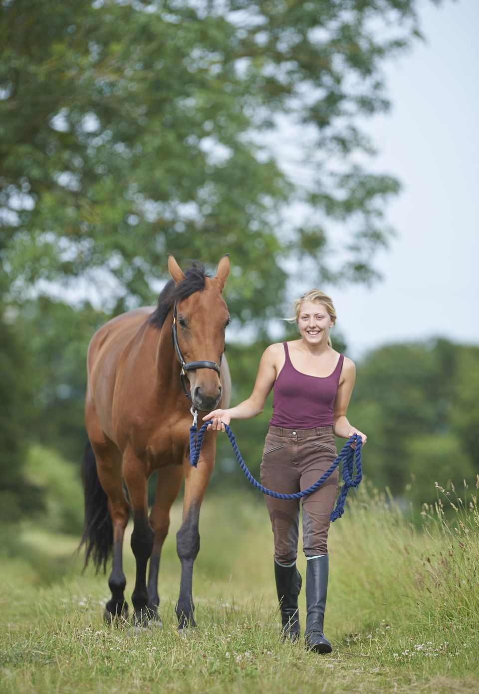 Young woman walking with horse in countryside.