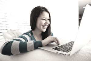 Teen girl chatting with friends on laptop