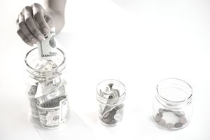 Woman depositing money into jars