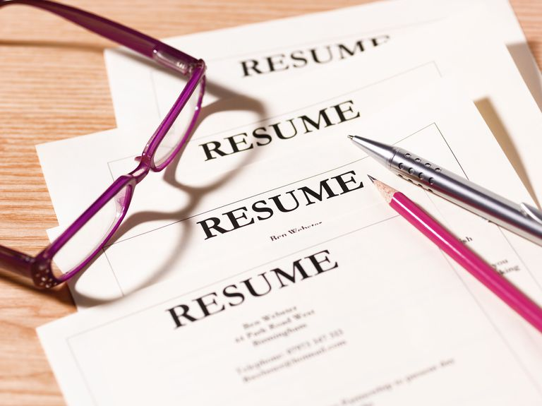 pile of resumes with glasses and pen