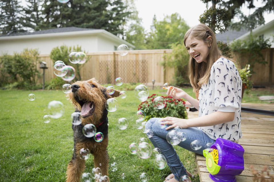 Woman enjoying her backyard, blowing bubbles around her dog.