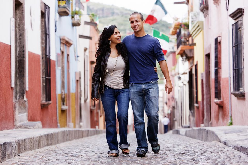 Hispanic couple walking on cobblestone stree