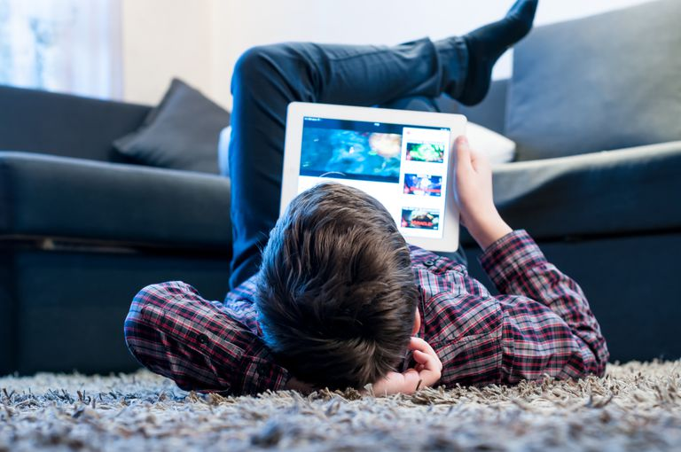 Teenager laying on the floor playing on a tablet