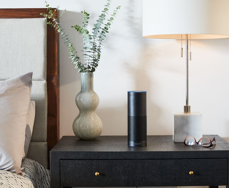 Night stand with lamp, vase, and a black Amazon Echo Plus