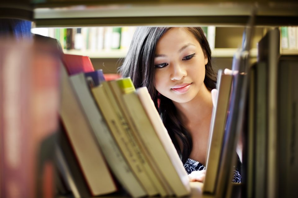 Girl looking through library at college
