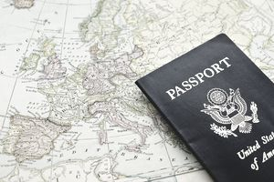 Close-up of passport lying on European map
