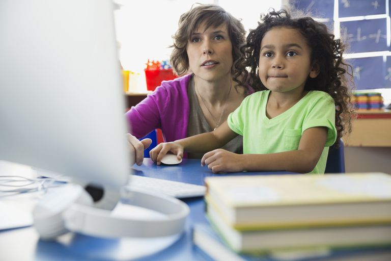 Teacher and girl using computer in elementary school