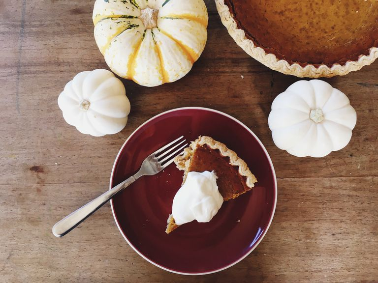 Directly Above Shot Of Pie In Plate With Pumpkins On Table