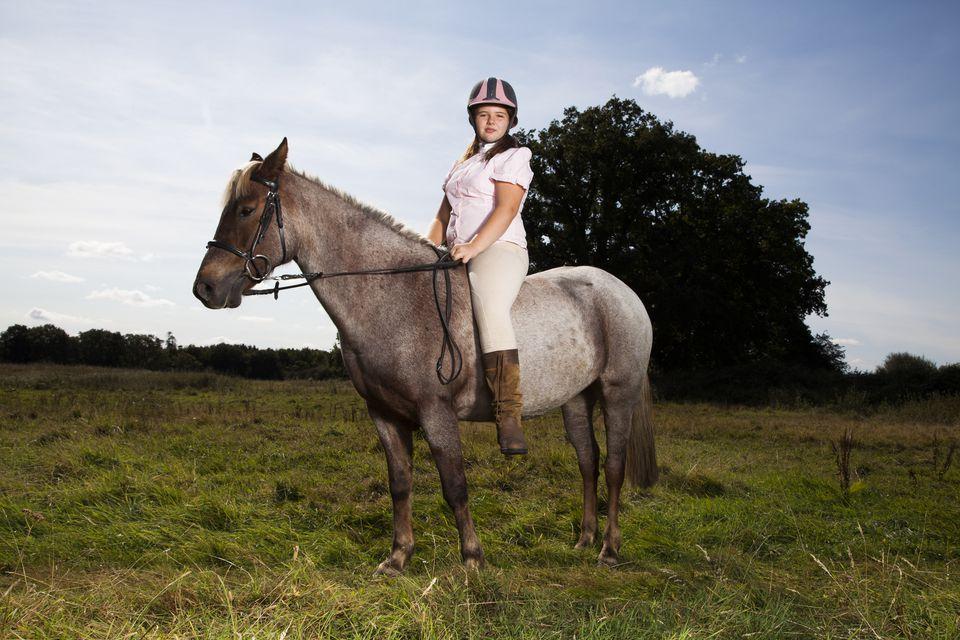 A girl sitting on pony bareback