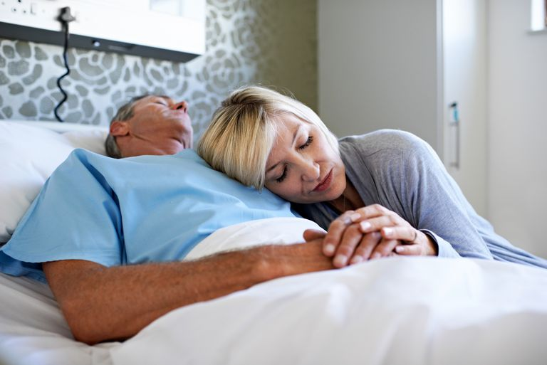 sick husband in hospital bed with wife comforting him