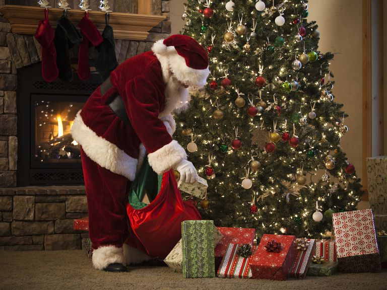 santa claus putting presents under the tree
