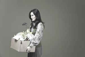 Fired businesswoman carrying her belongings in a cardboard box
