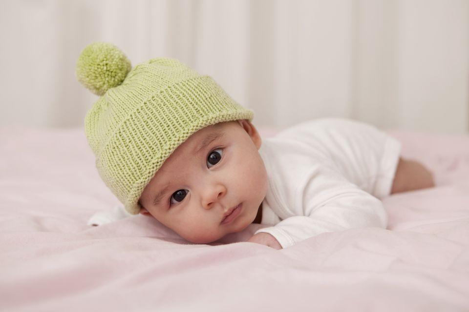 Baby boy wearing wooly hat lying on bed, portrait