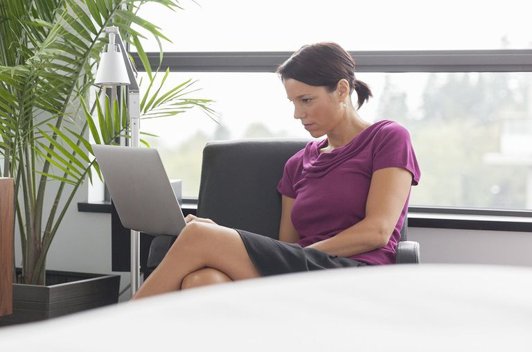 Woman using laptop in bedroom