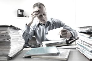 Businessman working in office with stacks of paperwork