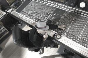 Music producer adjusting sound equipment
