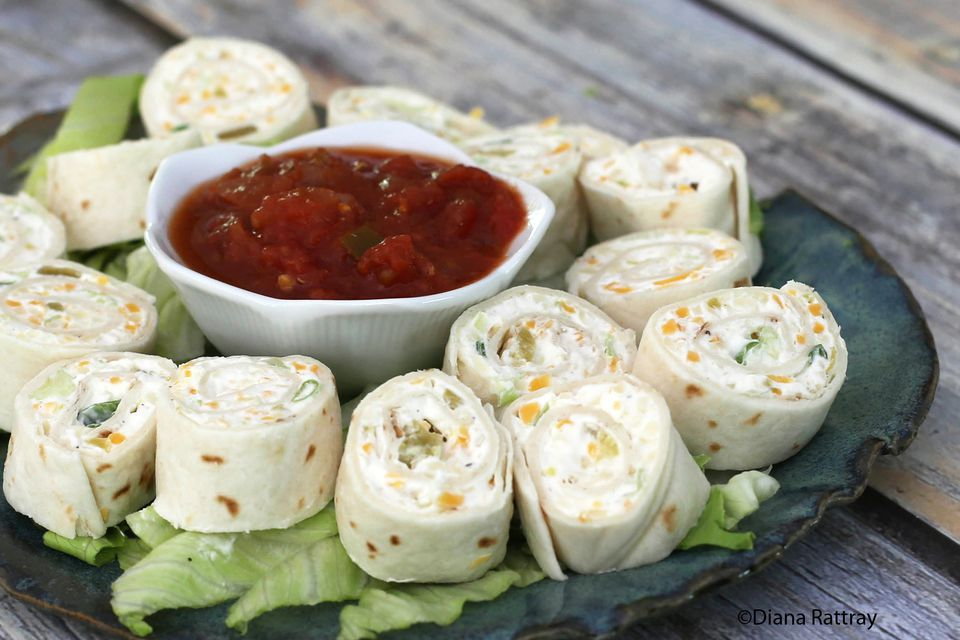 A plate of tortilla roll ups with salsa