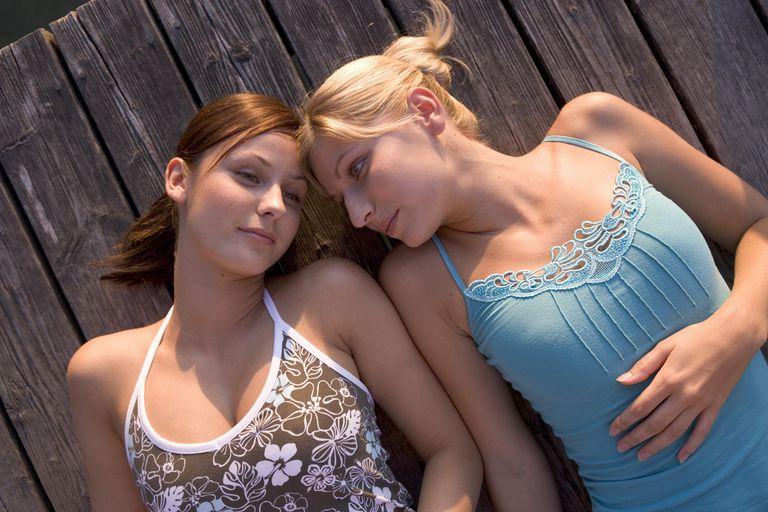 Two young women lying on boardwalk
