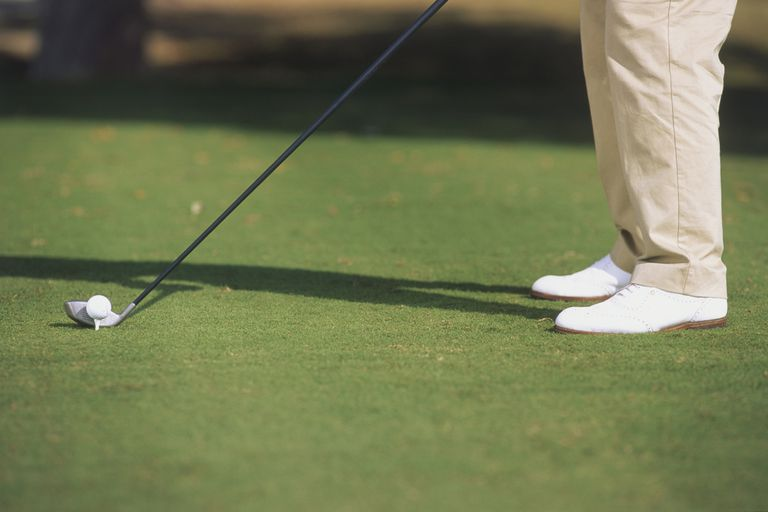 Golfer positioning golf club next to ball in grass, side view