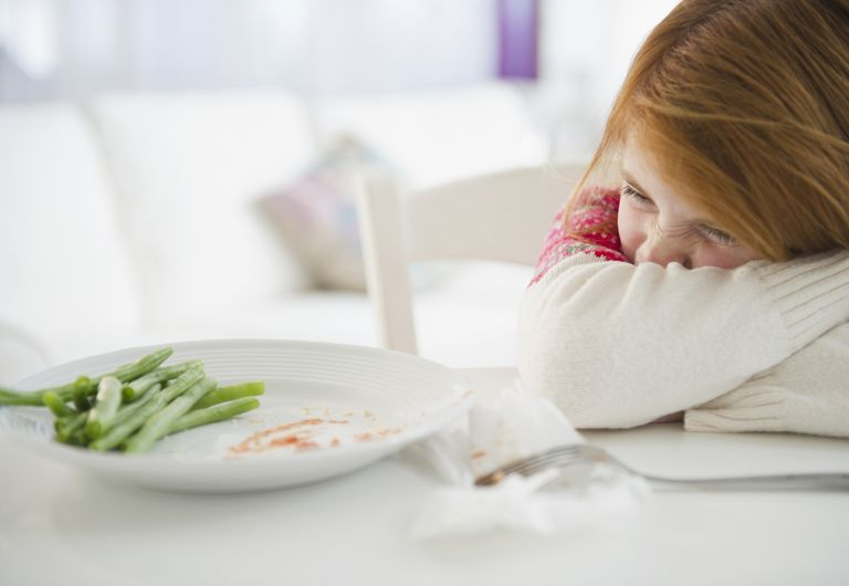 Young girl frowning at vegetables on dinner plate