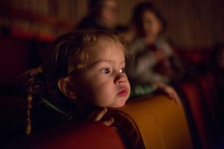 Caucasian girl watching movie in theater