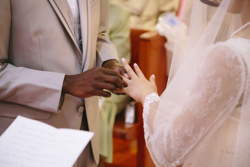 Bridegroom putting ring on brides finger at wedding ceremony