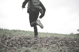Young man running through field