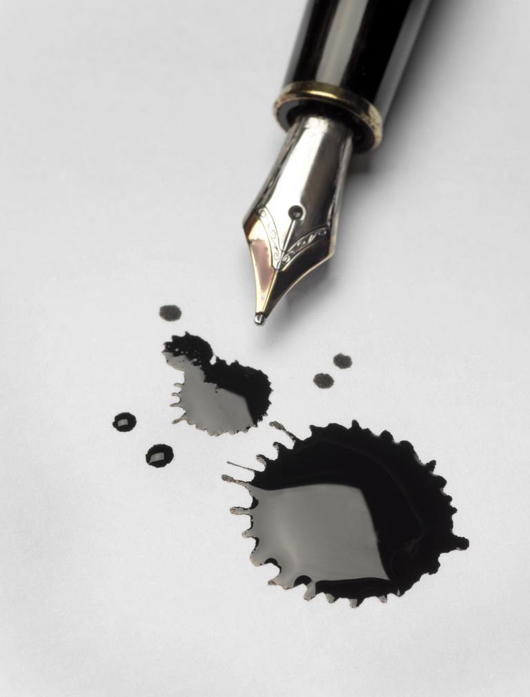 A calligraphy pen next to blots of ink.