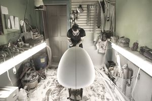 Shaper shapes a board at a Maine surf shop.