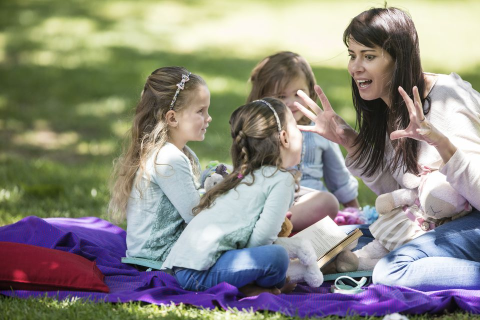 Mother telling stories to children on picnic blanket