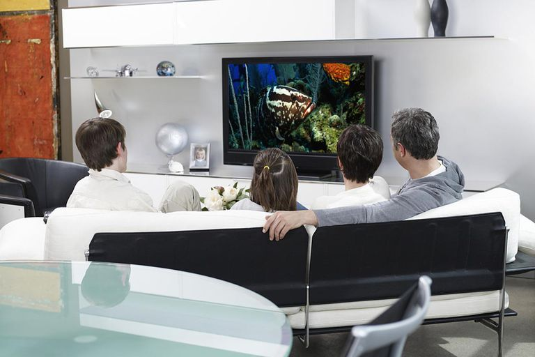 Family watching television in modern living room