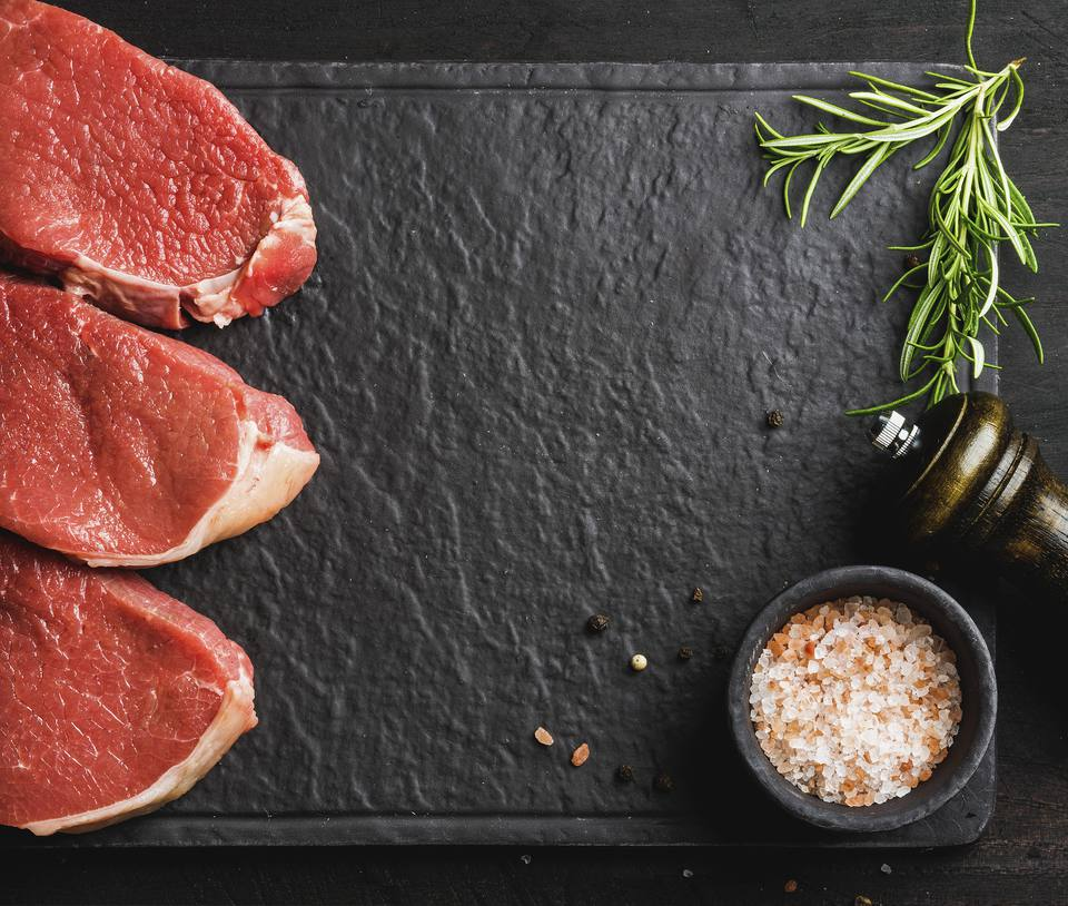 Raw beef Eye Round steaks with spices and rosemary on black slate stone board over dark wooden background, copy space