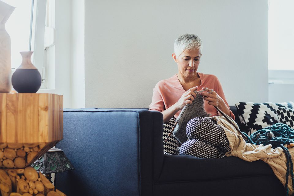 Woman knitting on sofa