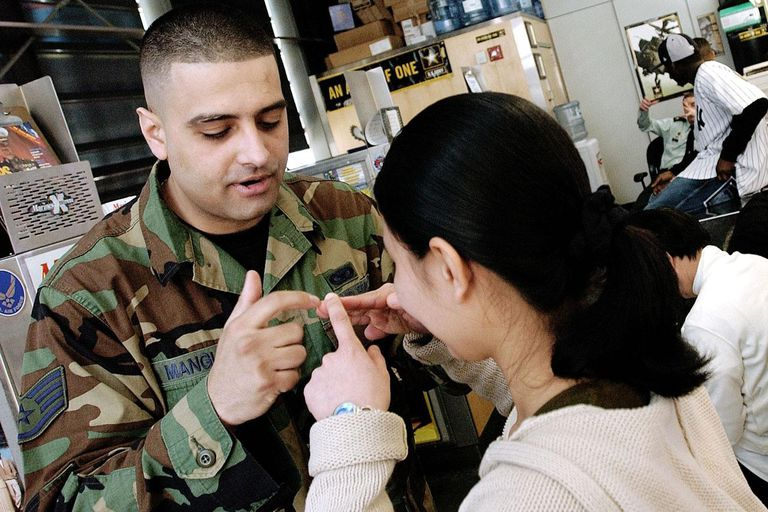 U.S. Air Force recruiter Staff Sergeant Dave Mangual (L) teaches Maricel Martinez, who reports to boot camp next week, the proper way to salute, March 14, 2003, at the Times Square U.S. Armed Forces Recruitment Station in New York City. As the U.S. military prepares for a possible war with Iraq, it has stepped up recruting efforts through television commercials, web sites and in-person visits.