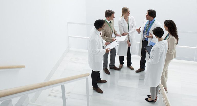 Business people and doctors meeting on landing of stairs
