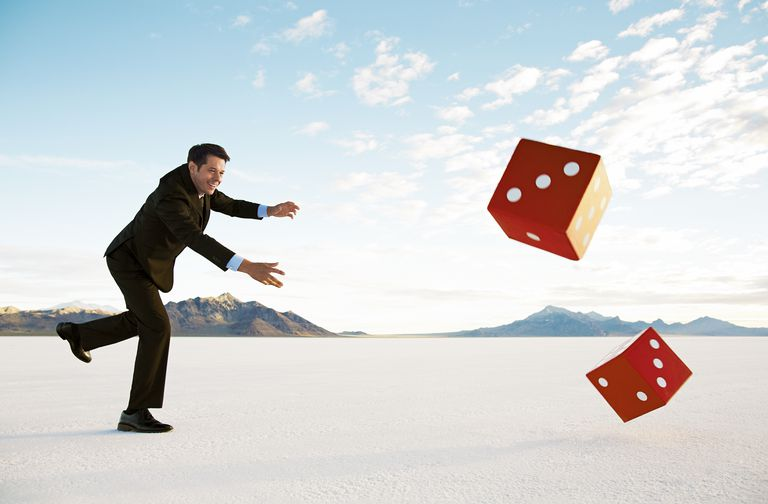 Businessman rolling giant dice on salt flats.