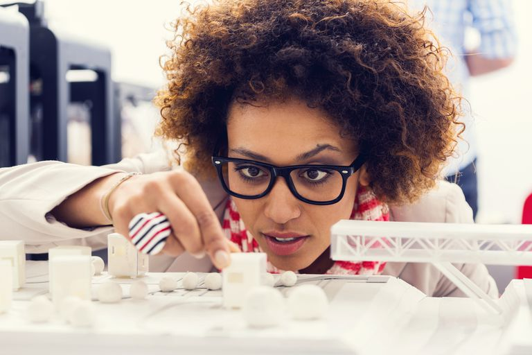 Close up of mixed race young architect sitting in a 3D printer office and watching 3D printings