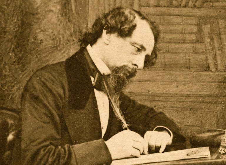 Photograph of Charles Dickens writing at a desk.