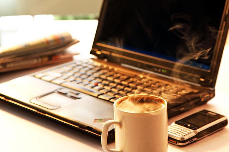 View of a coffee cup, laptop and a mobile phone