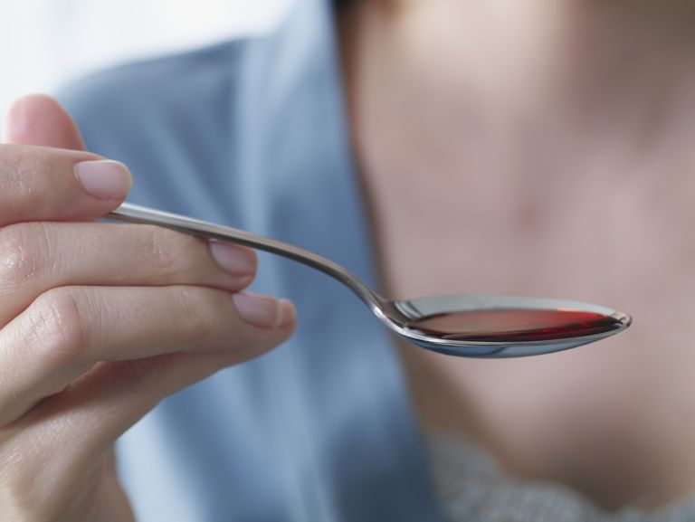 woman holding cough syrup on a spoon, taking it to improve hostile cervical mucus