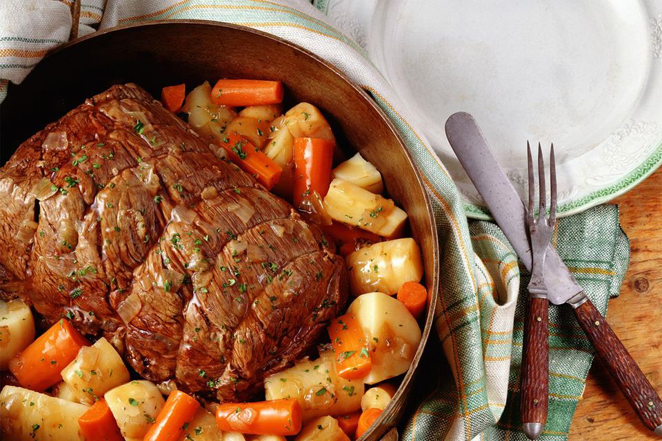 Pot roast with vegetables and potatoes on table