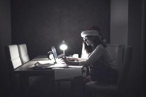 Woman wearing Santa hat working on a laptop