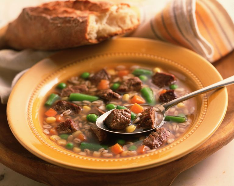 Beef and vegetable soup with spoon and bread
