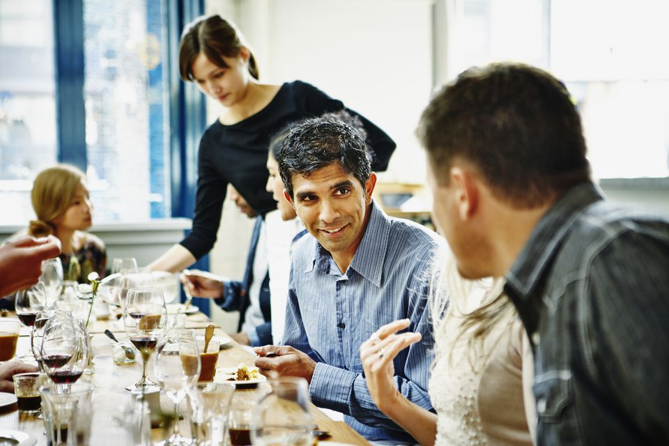 Man in discussion with friends during dinner party