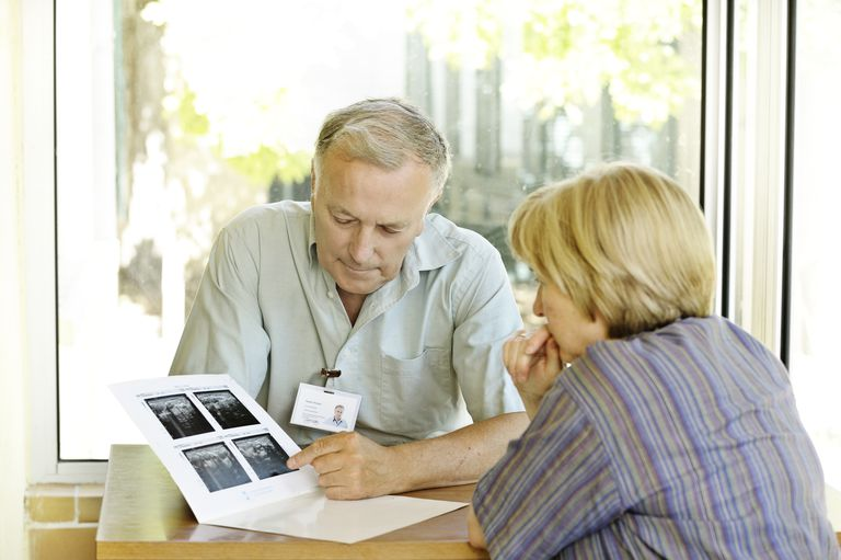 Male physician specialist explaining scans to female patient ** ID badge made entirely by photographer ** Specialist doctor explains scans to woman. The scans are blurred for varied use but are actually scans of the uterus for gynaecological tests.