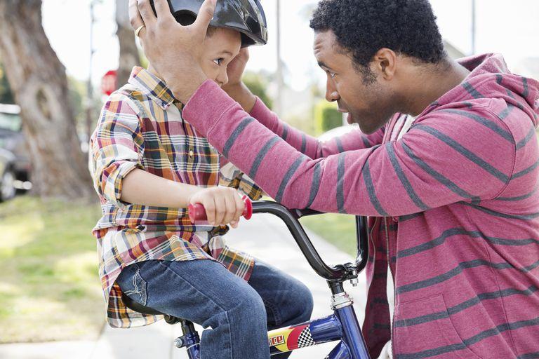 father adjusting son's bike helmet