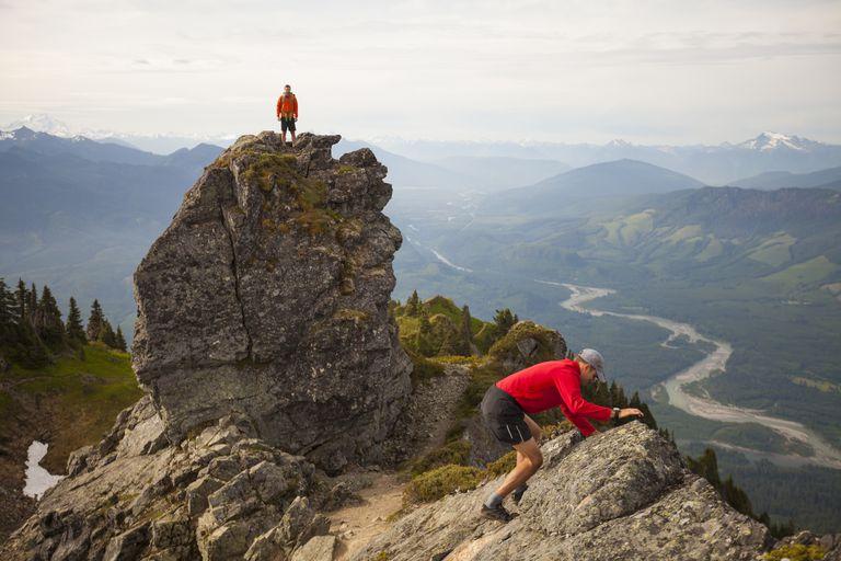 Two backpackers enjoy climbing and scrambling on the many summits of Sauk Mountain, Washington.