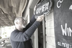Senior male vintner hanging open sign at winery tasting room